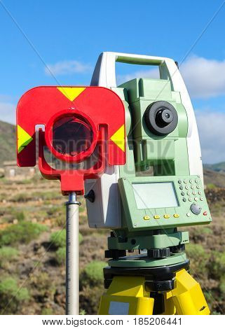 Close up of modern surveyor equipment theodolite with prism used in surveying and building construction for precise measurement. Total station outdoor at construction site. Copy space.