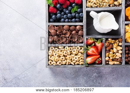 Variety of cold quick breakfast cereals with berries in old gray wooden box and other ingredients for breakfast, healthy eating concept, top view. Copy space.