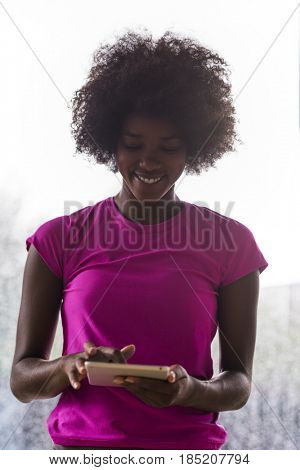 beautiful african american woman using tablet computer from home while rain and bad weather is outdoor