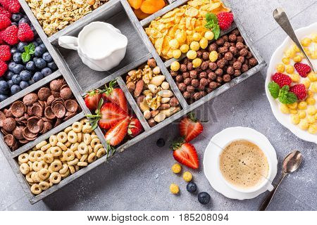 Healthy breakfast with coffee, variety of cold quick cereals and berries in old gray wooden box, top view.