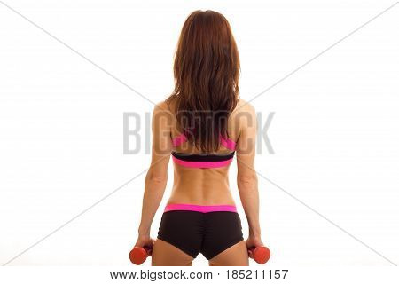 athletic young girl with supple buttocks in black shorts turned back to the camera and holding a dumbbell isolated on white background