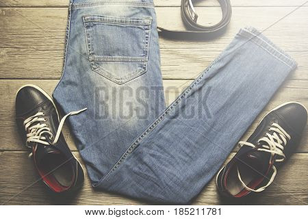 man jeans belt and sport shoes on wooden background