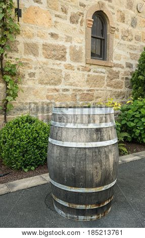 Wooden wine barrel standing by warm stone walls and window of ancient winery in Napa Valley California