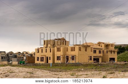 Wooden sheathing on exterior of new townhouses and single family homes in California with dark clouds to suggest recession