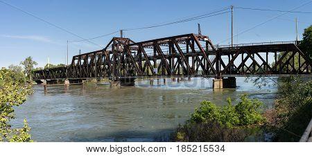 Metal truss swing bridge called I St Bridge across flooded Sacramento River in capital of California