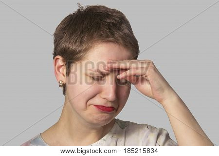 Sad Girl In A Depression With A Hand Pressed To Her Forehead And A Short Haircut Is Isolated On A Ne