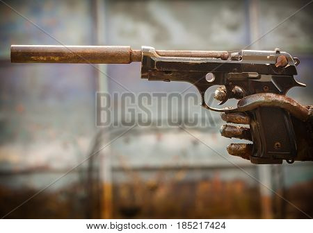 The hand holds a pistol with a silencer. The gun is not combat.