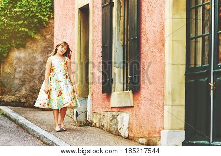 Adorable kid girl walking down the street, wearing party dress and silver mirror shoes