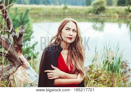 Autumn girl standing watching nature. Autumn forest colors with girl back view. Outdoor autumn landscape. Orange autumn portrait.