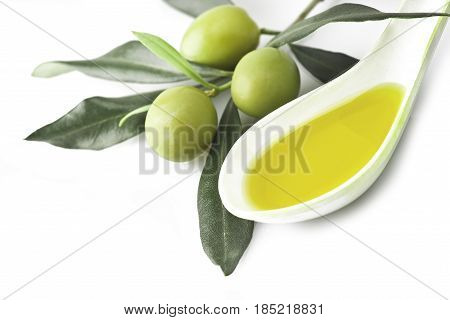 Branch with olive leaves and olives on wooden table