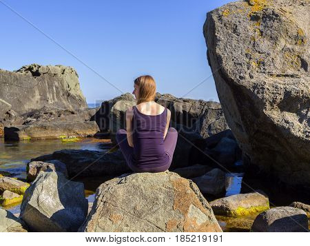Woman practices yoga near the sea, on the rock, slow motion hd video
