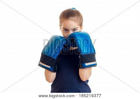 little girl wore at the hands of the big boxing gloves and covering her face isolated on white background
