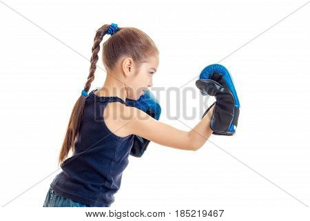 little girl with pigtail stands sideways in boxing gloves is isolated on a white background
