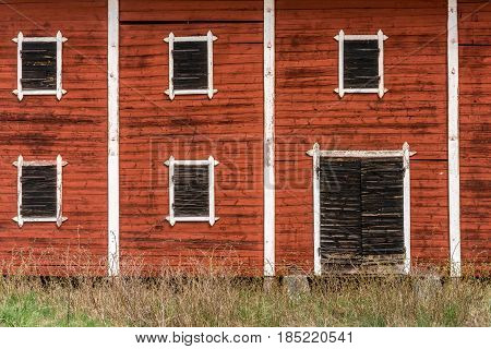 Exterior of an old abandoned decayed red barn with closed wooden window shutters.