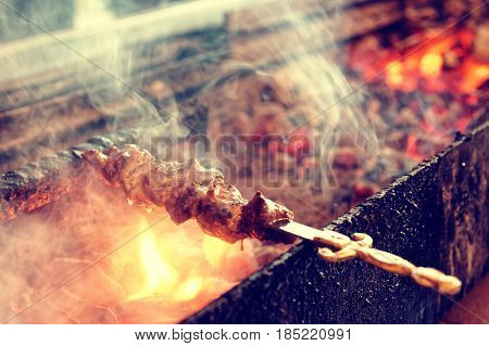 Spit roasted meat being fried on a charcoal grill, toned image
