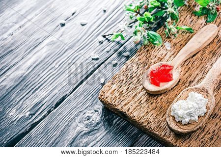 Ricotta or farmers cheese and red jelly in rustic wooden spoons. Textured black wood background with apple blooming twigs. Selective focus