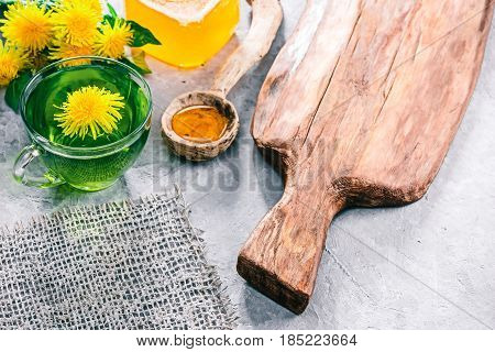 Green mint tea in translucent glass tea cup and honey in rustic spoon on concrete background with dandelions