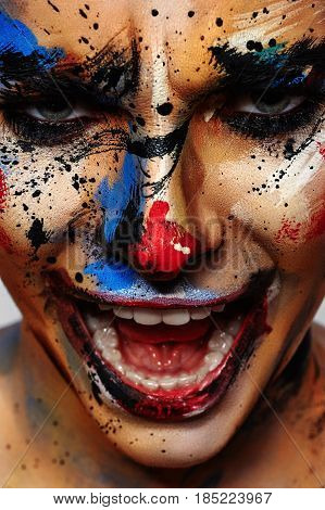Portrait of laughing insane Clown with black, blue, red and yellow Paint Splashes on Face