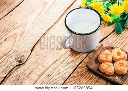 Buttermilk in metal mug and cookies. Raw wood background with dandelions. Selective focus