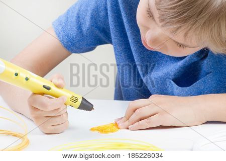 Schoolboy with 3d printing drawing pen. Creative, leisure, technology education concept