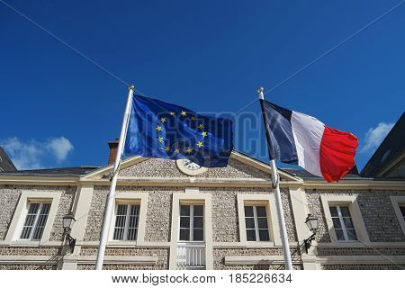 Flags of France and European Union waving in wind. Flag of Europe. French national official flag. Symbol of partnership in EU