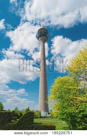 TV tower Rheinturm Dusseldorf Germany Europe. Famous Rhine Tower is a 240.5 metre high telecommunications tower tallest building in Dusseldorf. View from park. Modern european architecture