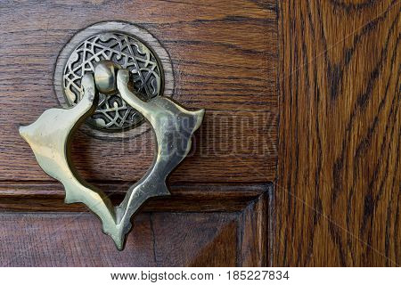 Closeup of antique copper ornate door knocker over an aged wooden door Fatih Mosque Istanbul Turkey