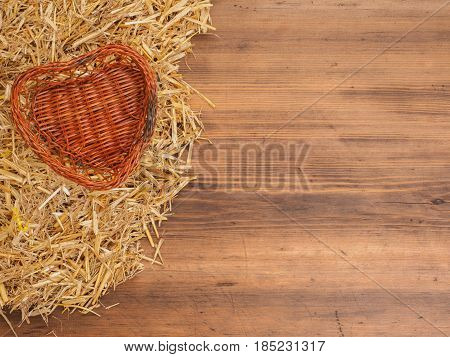 Rural eco background. Wicker-work basket from withe in heart shape with straw on the background of old wooden planks. The view from the top. Creative background for greeting cards, menu or advertising