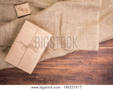 Vintage gift box on old wood planks and burlap vintage background, photo top view. Gift box wrapped in craft paper and tied with string. Rural background for greeting cards. Top view