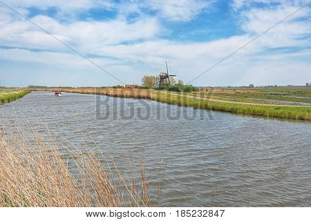 Typical Dutch polder landscape with mill and powerboat in the canal