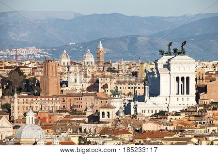 The roofs of Rome, Italy. Mountains of Lazio. An aerial view of the roofs of the ancient city of Rome in Italy. Some churches with domes, in the right altar of the homeland white building.