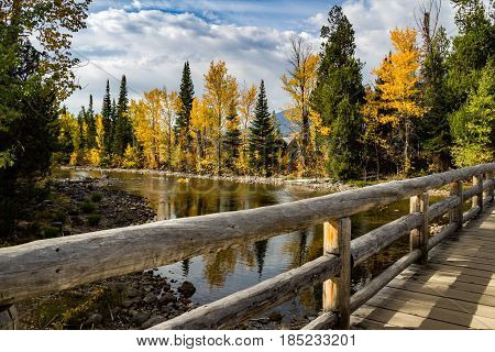 Wooden walkway over river with pine and aspen reflections