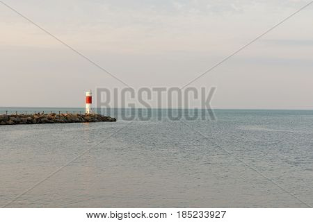 Wide angle view of red and white lighthouse on Lake Ontario Shore.
