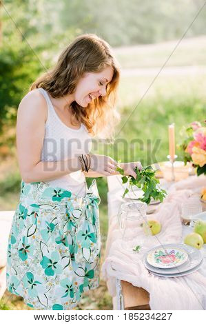 picnic, people, food, summer, holiday concept - young beautiful smiling woman prepare mint leaves to lemonade in glass flagon on table around festive plates, pear fruits, bouquet of flowers, candles