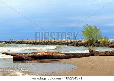 Rough surf on Lake Ontario near Rochester, New York, during a stormy evening, with driftwood in foreground and a rocky quay in the background