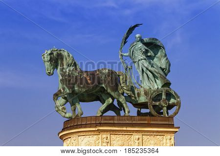Statue representing Peace, a woman holding a palm frond on a chariot, on a colonnade in Heroes Square or Hosok Tere by day, Budapest, Hungary.