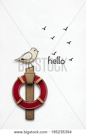 Creative photo of a bird with a flotation ring made of paper on white background.