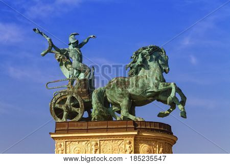 Statue representing War, a man holding a snake on a chariot, on a colonnade in Heroes Square or Hosok Tere by day, Budapest, Hungary.