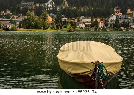 A small brown wooden boat under a yellow tarpaulin on the lake of St. Moritz. (Engadin Grisons Switzerland)