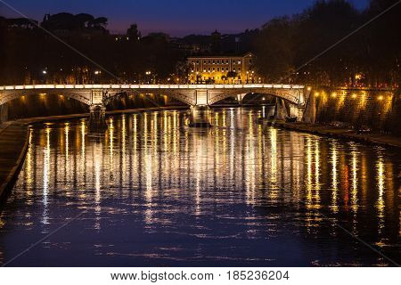 Tiber River, bridge (Ponte Giuseppe Mazzini) and reflections on water. Night. Rome, Italy. Historical building at the top.