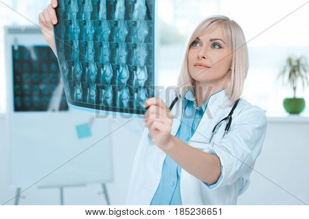 Young woman doctor standing in the office at hospital holding x-ray