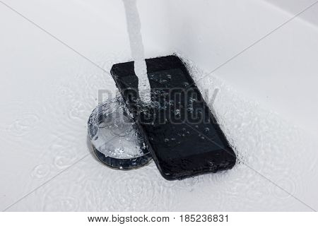 black mobile phone falling into washbasin flowing with water jet