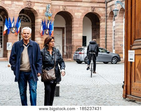 STRASBOURG FRANCE - MAY 7 2017: French city with Adult couple exiting polling place during the second round of the French presidential election to choose between Emmanuel Macron and Marine Le Pen