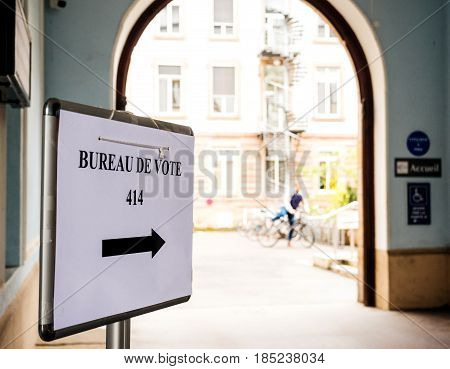 Silhouette of cyclist next to bureau de vote sign in French city next to pooling place during the second round of the French presidential election to choose between Emmanuel Macron and Marine Le Pen