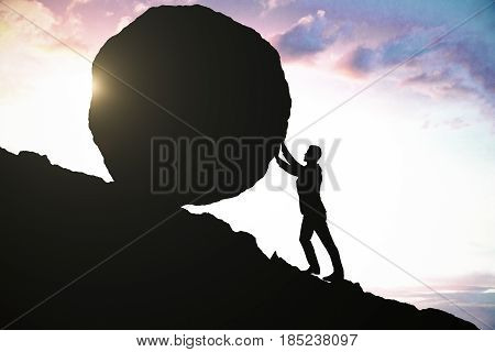 Side view of male silhouette pushing huge rock uphill. Beautiful sky background. Determination concept