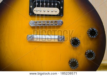 Part of the soundboard of an electric guitar brown closeup