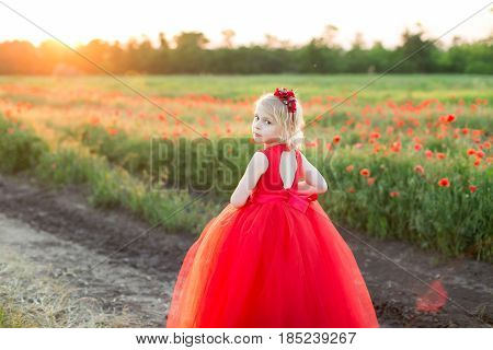 girl model, childhood, fashion and summer concept - girl blonde in red dress standing half a turn on the road near the field with poppies, on the back of her dress neckline, on head a red headband