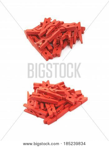 Pile of red painted wooden clothespins isolated over the white background, set of two different foreshortenings