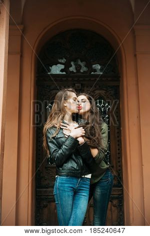 Pretty Girls Kissing And Hugging In Jeans On Front Door