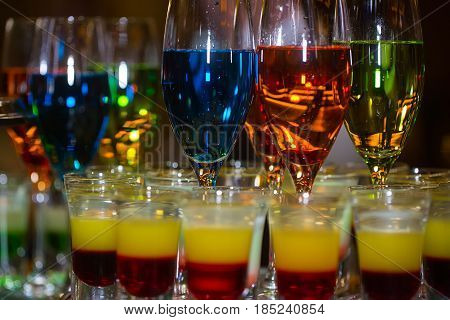 Variety of layered shots and mixed cocktails colorful alcoholic beverages in glasses served in rows in bar or night club on blurred background. Entertainment and lifestyle